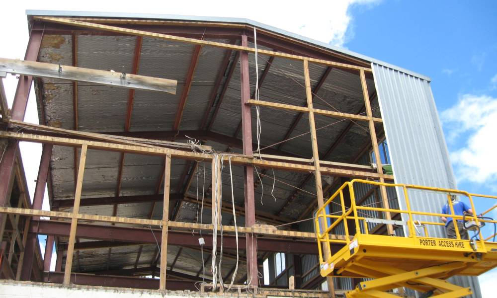 A worker on a scissor lift removing corrugated iron off the side of a commercial building