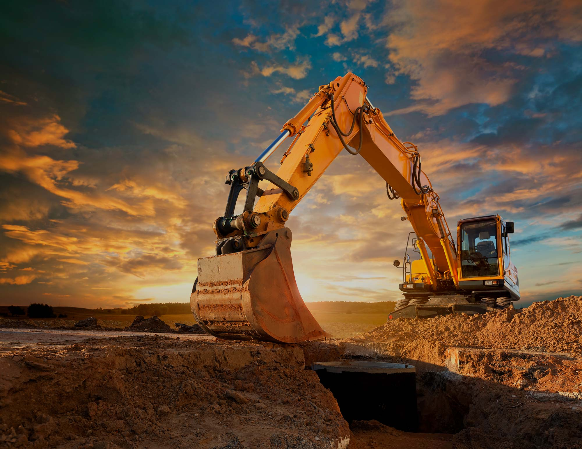 A yellow digger sitting on top of a pile of clay with the sun setting in the background