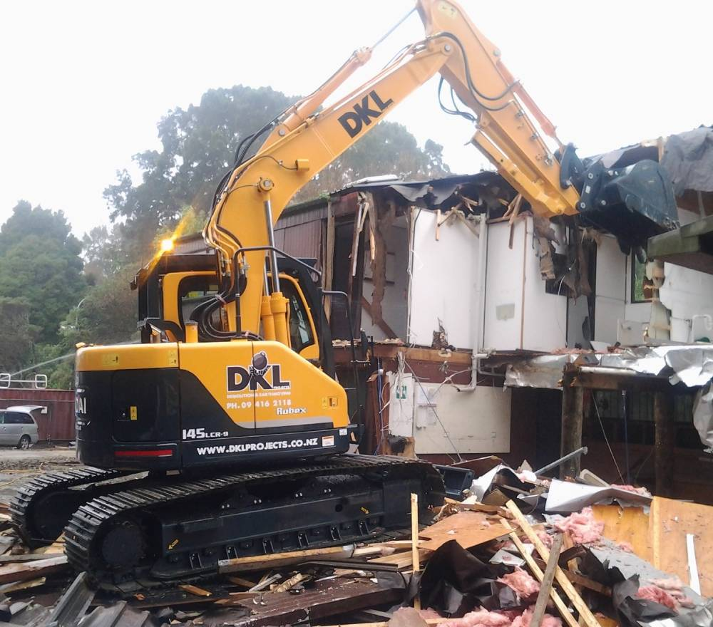 A yellow excavator demolishing the wall with its digger claw of a residential property