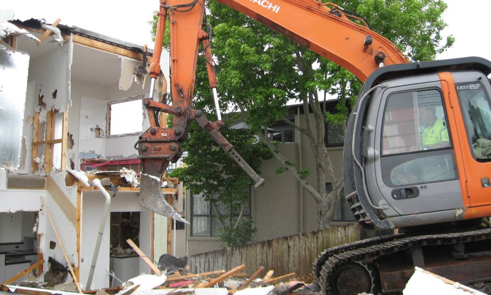 An orange excavator pulling down the wall of an residential building