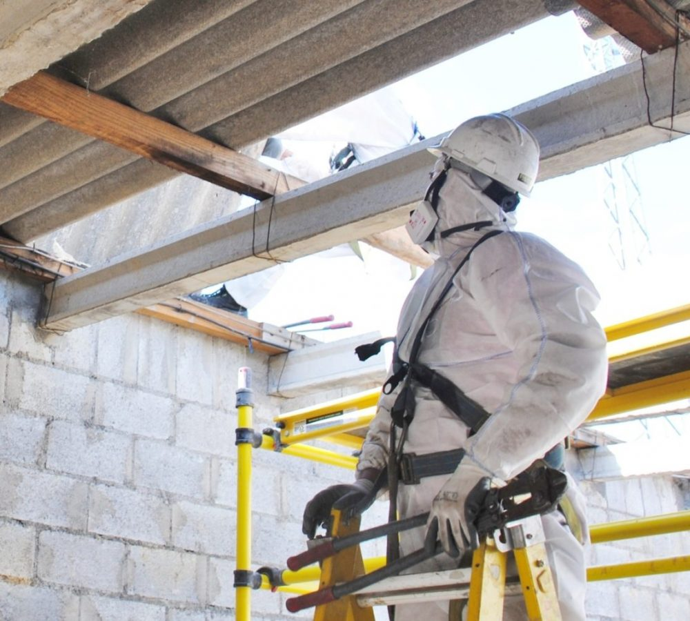 A worker on a step ladder in full protective gear performing asbestos removal