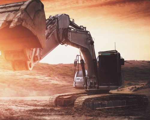 A black excavator with it's digger towards the camera digging at sunset