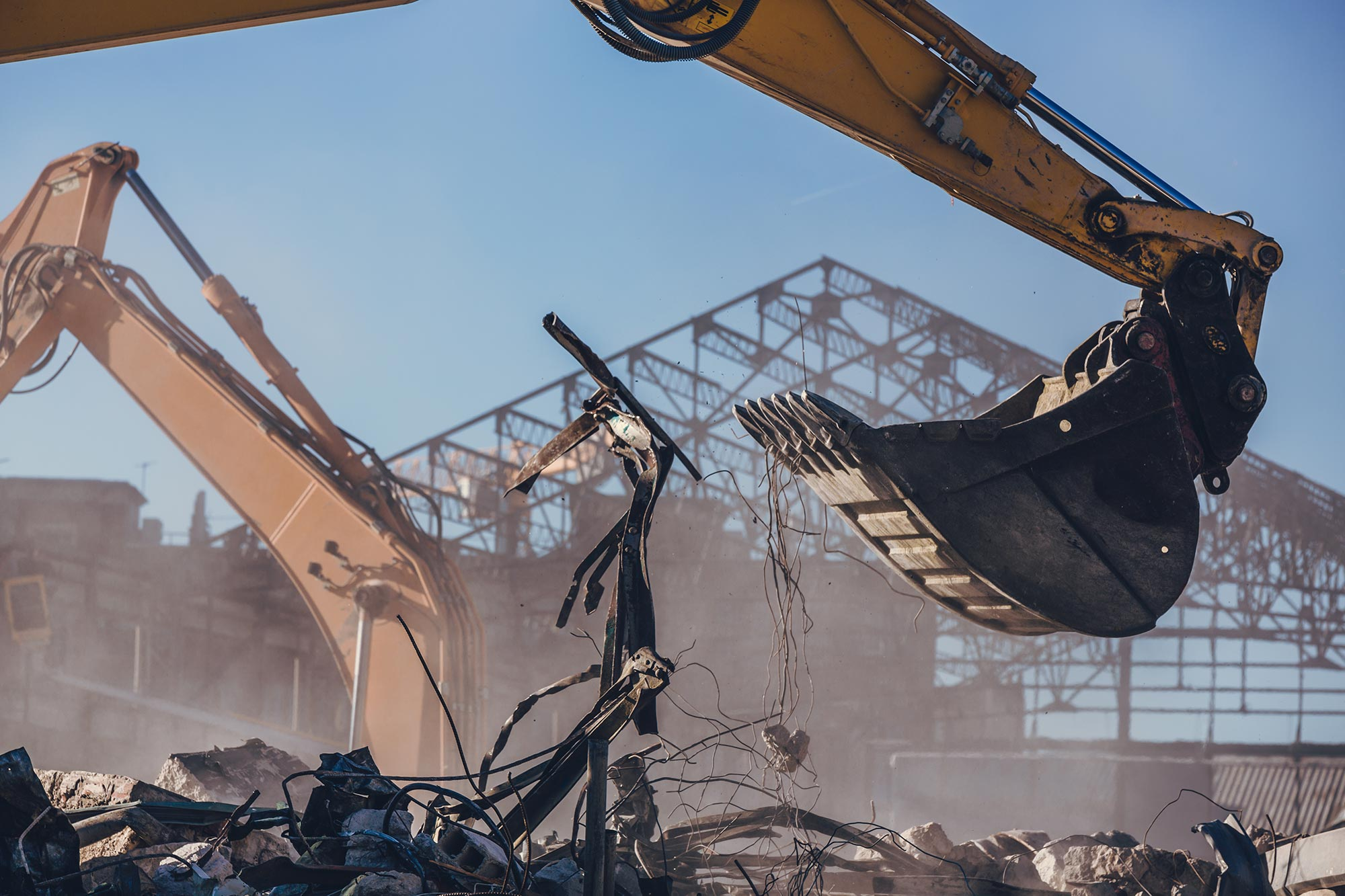 An excavator arm amidst debris with the structure of an industrial building in the background