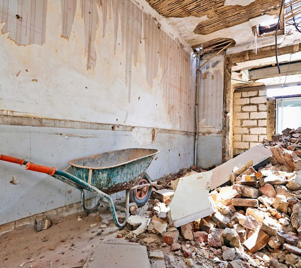 The interior of a building that is being demolished with broken down walls and rubble, with a wheelbarrow in the foreground.