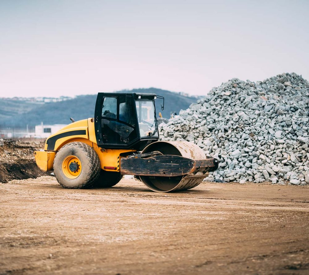 A road roller operating in front of a pile of rubble and debris
