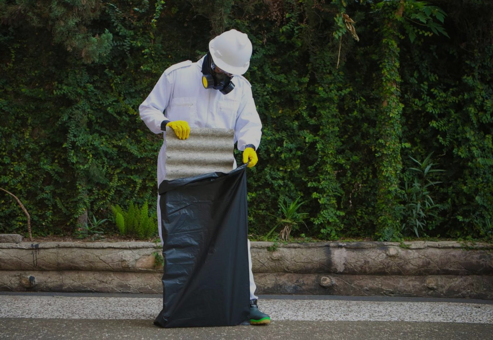 A worker, in full protective gear, disposing of asbestos lined corrugated iron