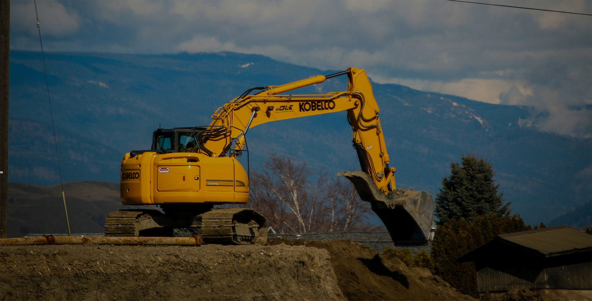 An excavator on a work site digging a hole