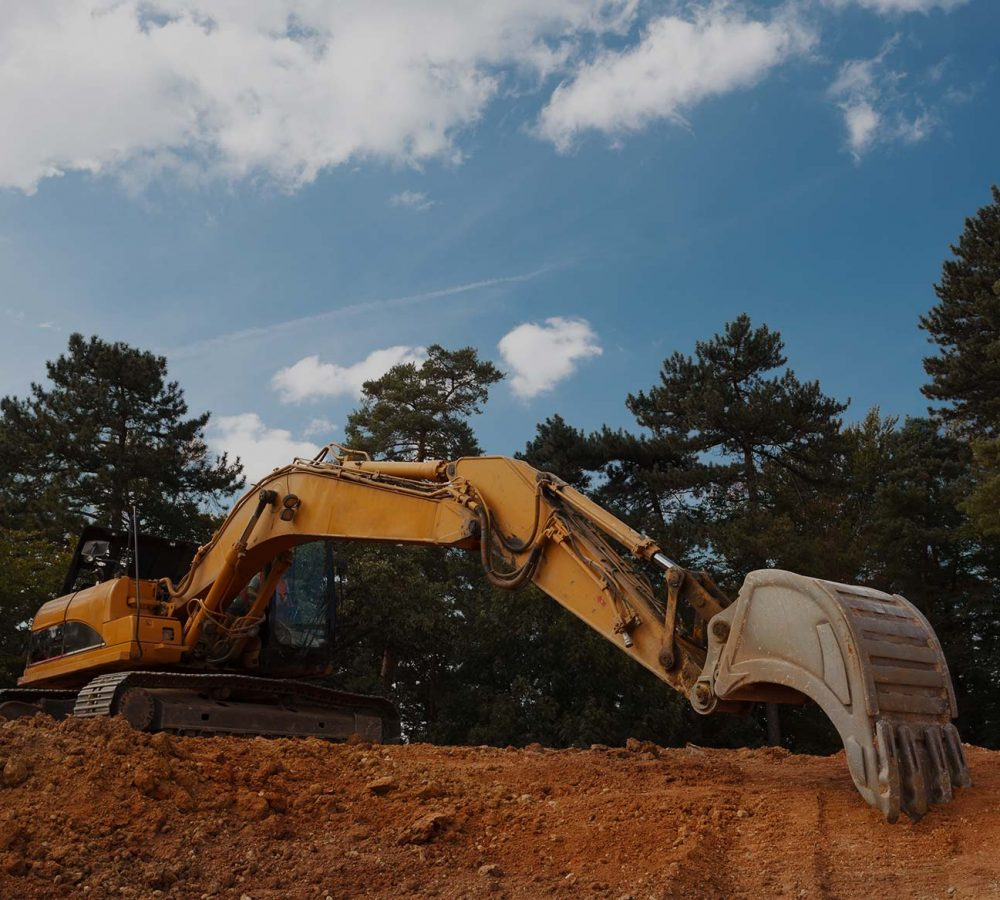 An excavator using its arm to perform earthworks on a site